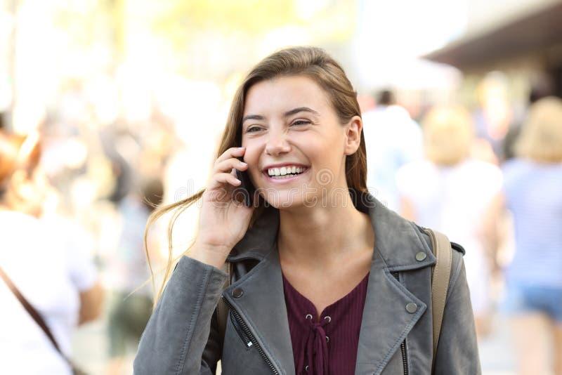 青少年笑,当谈话在电话时 库存照片