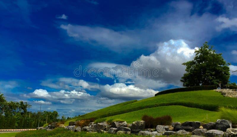 青山、绿色树,云彩和蓝天美丽的景色 免版税库存照片