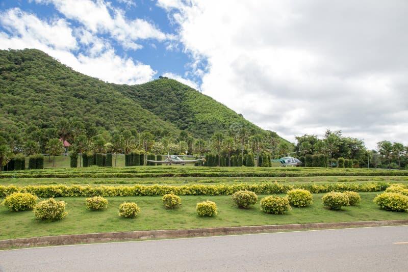 青山和树庭院豪华的草,与白色云彩的天空蔚蓝 库存照片