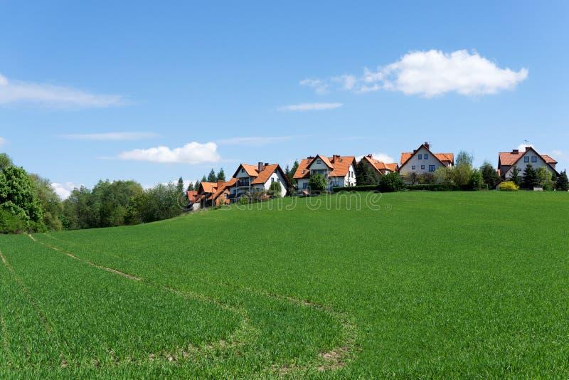 青山的红色被顶房顶的房子 免版税库存图片
