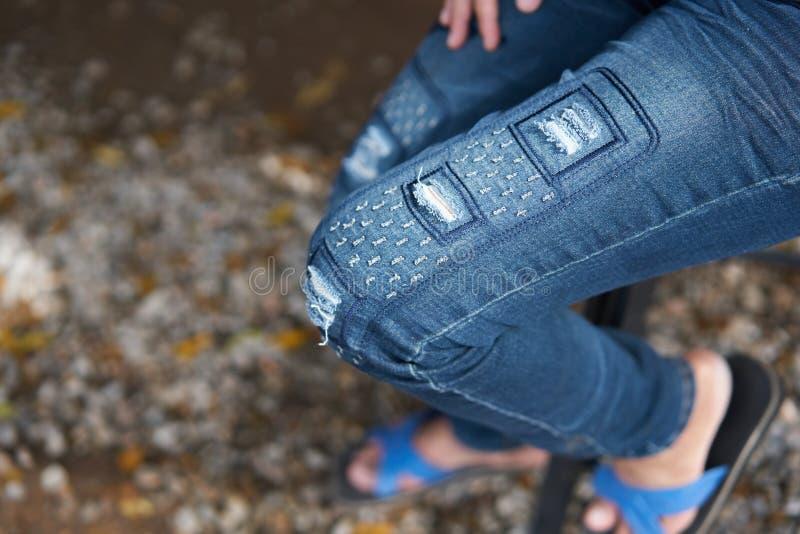 青年人佩带的蓝色困厄的牛仔裤,被剥去的牛仔裤,被撕毁 库存图片