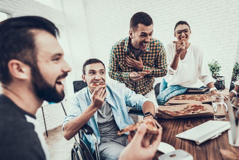 青年人吃午餐用薄饼在办公室 免版税库存图片