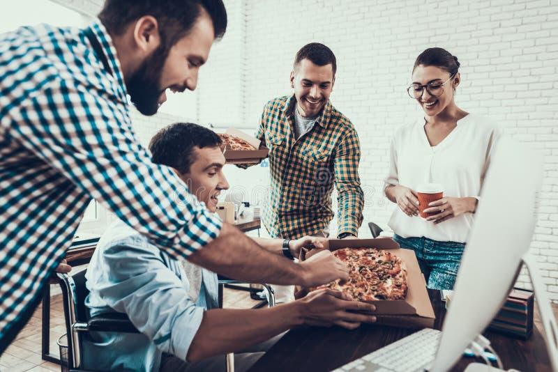 青年人吃午餐用薄饼在办公室 免版税库存照片