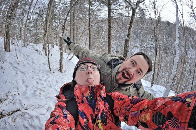 青年人夫妇获得乐趣在冬天森林 免版税库存图片