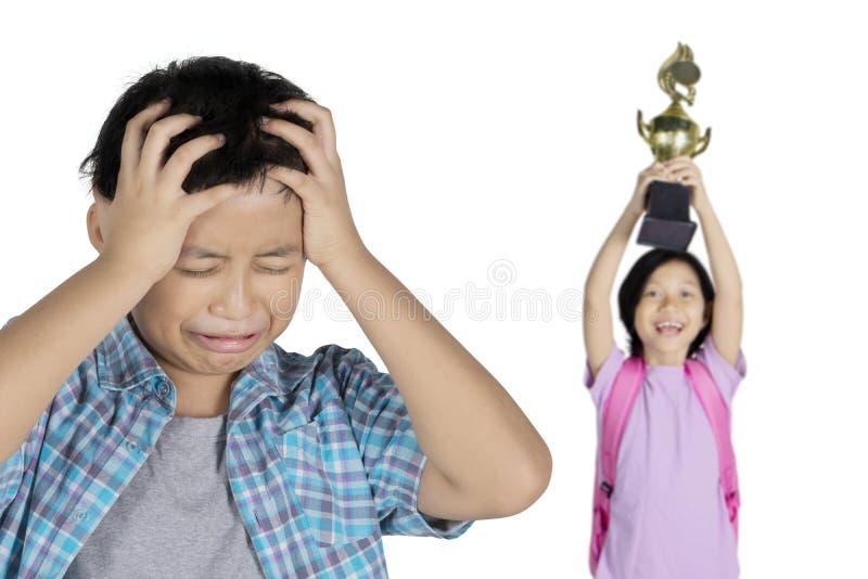 青春期前的男孩羡慕看与他的姐妹 库存图片