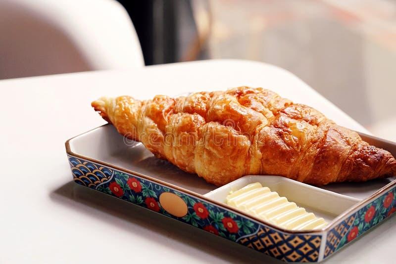 青纹干酪新月形面包供食用黄油 背景的一个餐馆场面 早餐板材用新近地被烘烤的新月形面包 免版税图库摄影
