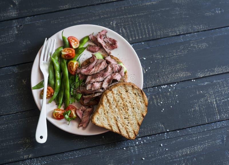 青豆和烤牛排在多士牛排三明治和青豆-健康快餐在黑暗的背景 免版税库存图片