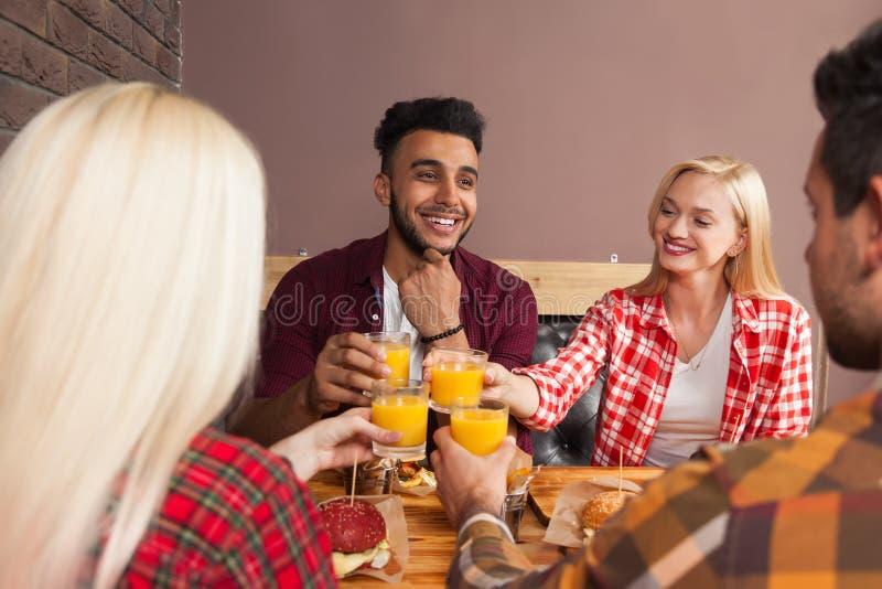 青年人小组男人和妇女在汉堡咖啡馆,敬酒橙汁命令快餐坐木表 图库摄影