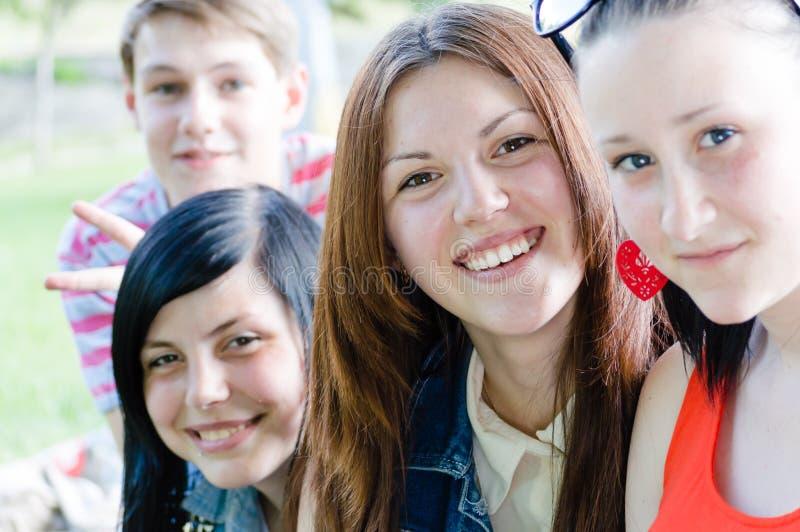 青年人少年朋友愉快微笑&看照相机在夏天户外 库存照片