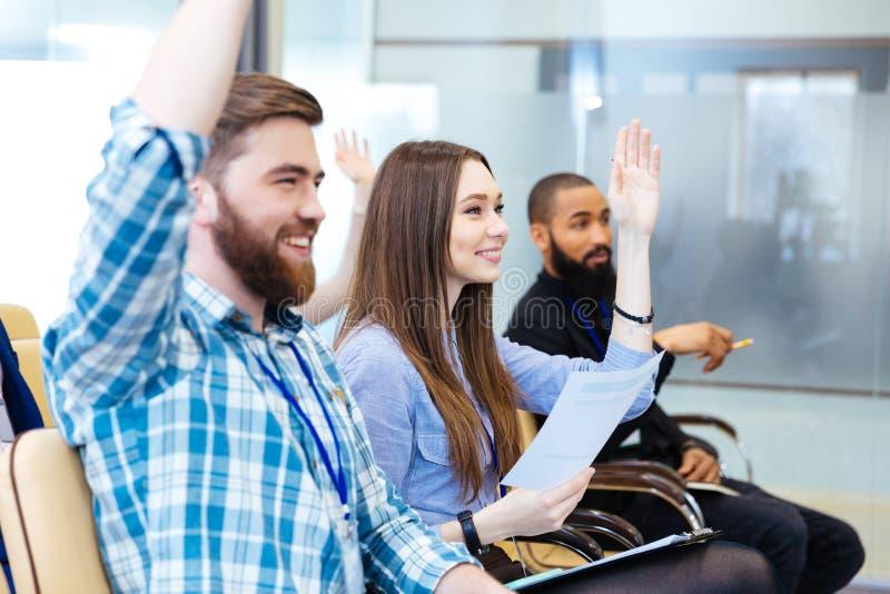 青年人用被举的手坐业务会议 免版税库存图片