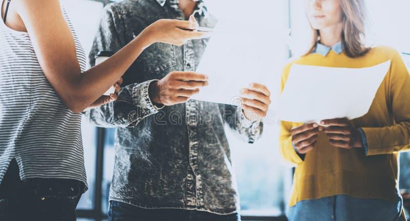 青年人谈论企业想法在办公室 供以人员拿着本文他的手和谈话与妇女 水平 免版税库存照片