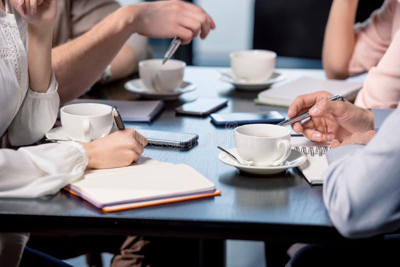 青年人饮用的咖啡特写镜头部份视图和写在笔记本在业务会议上 免版税图库摄影