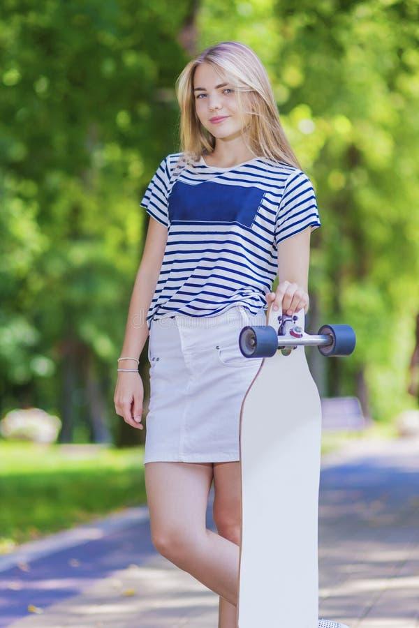 青年生活方式概念 摆在与长的滑板的白肤金发的白种人十几岁的女孩 图库摄影