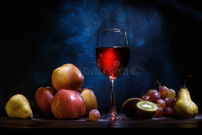 静物画、苹果、葡萄、果子和红色汁液在深蓝背景 免版税库存照片