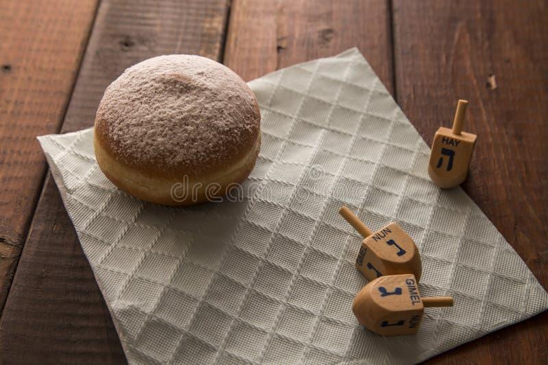 静物画为犹太假日光明节用多福饼和在木土气桌上的3 dreidels 库存照片