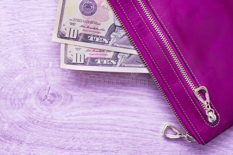 静物画以紫罗兰色样式、紫色皮革钱包和美国美元在木背景 库存图片