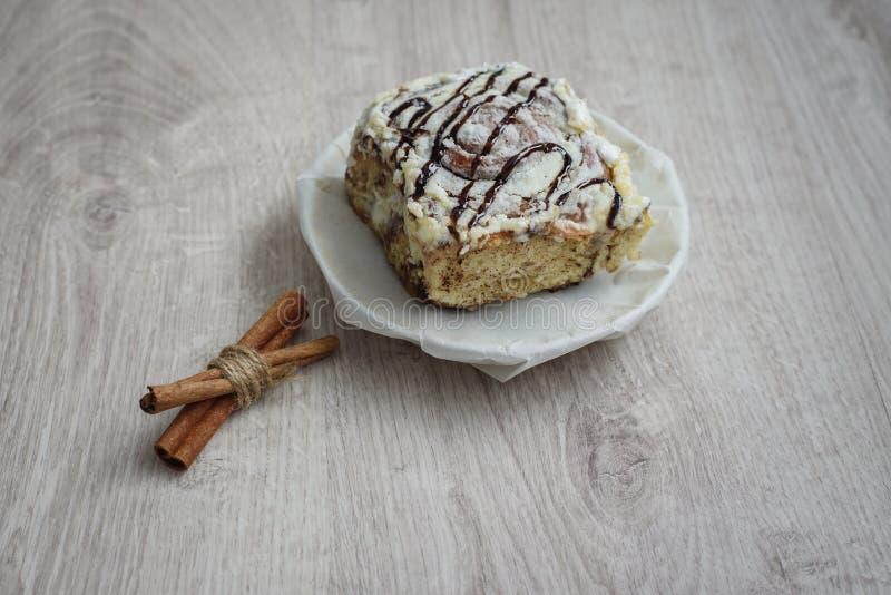 静物画可口切片在一个茶碟和肉桂条的甜蛋糕在木背景 免版税图库摄影