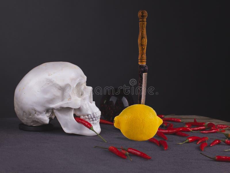 静物画头骨用黄色柠檬、刀子和红辣椒 尊敬 库存照片