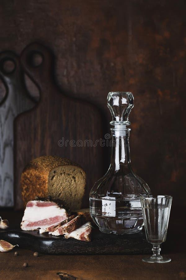 静物画用伏特加酒、面包和猪油 库存照片