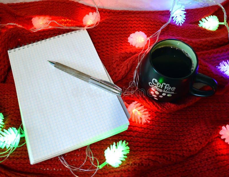 静物画用咖啡和笔记本在红色背景 库存图片