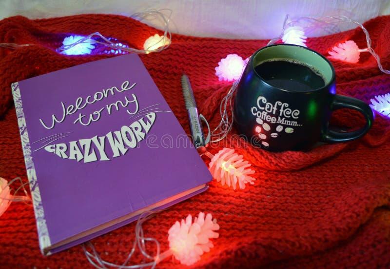 静物画用咖啡和笔记本在红色背景 免版税库存图片