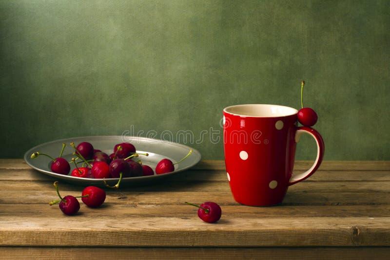 静物画用樱桃和红色杯子 免版税库存图片