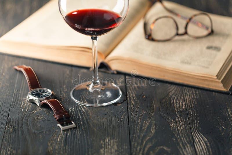静物画用红葡萄酒和旧书在老木桌上在减速火箭的样式 库存图片