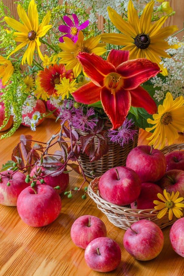 静物画用苹果和花 夏天或秋天 黄色花和红色苹果 免版税库存照片