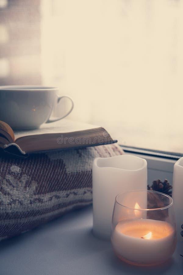 静物画细节在家内部的 毛线衣,杯子,羊毛,舒适,书,蜡烛 喜怒无常 舒适秋天冬天概念 免版税库存照片