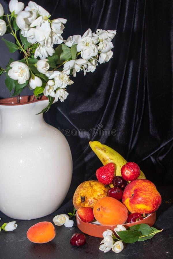 静物画,在那里一个白色水罐是茉莉花分支和在它旁边是果子 免版税库存照片