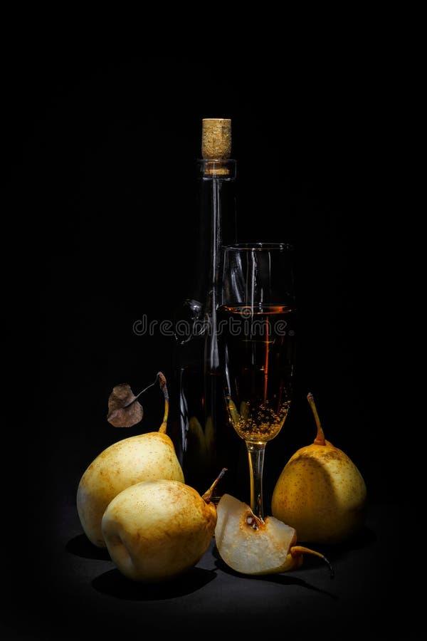静物画;瓶酒、整个梨和一半在黑暗的背景 库存照片