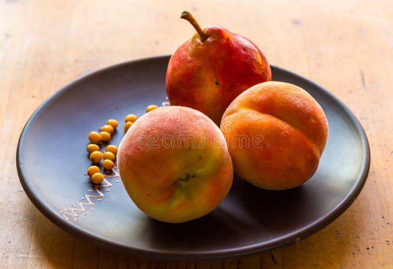 静物画-水多的柔软光滑的桃子、大成熟梨和海鼠李莓果在一块陶瓷板材在木背景 图库摄影