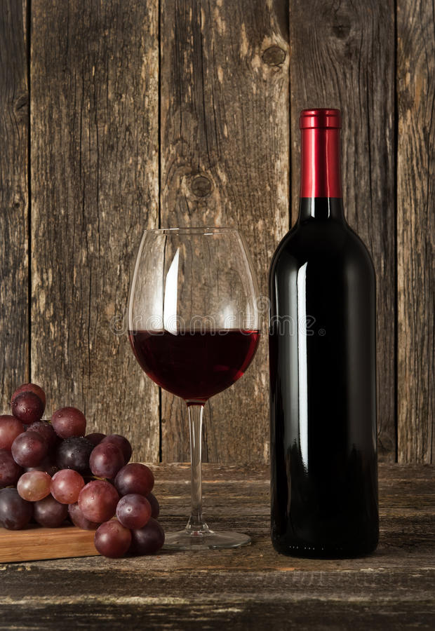 静物画。瓶红葡萄酒、玻璃和葡萄 库存照片