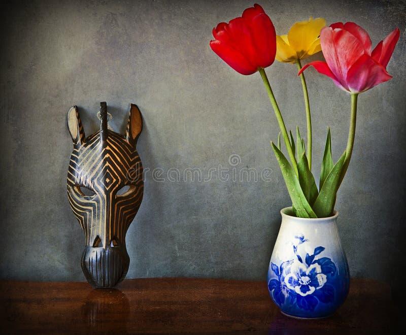 静物画-与花和非洲面具的内部 免版税库存照片
