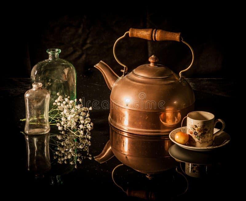 静物画古色古香的黄铜茶罐,杯子,花 免版税图库摄影