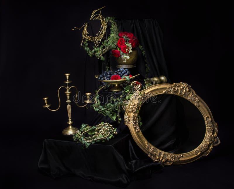 静物画开花在布织品的玫瑰金黄烛台花瓶葡萄 库存照片