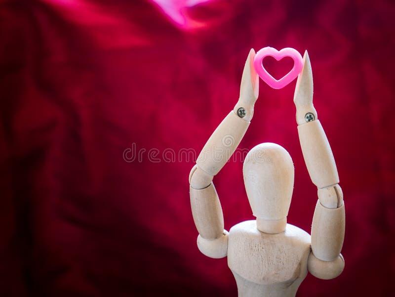 静物画木木偶和桃红色心脏 免版税图库摄影