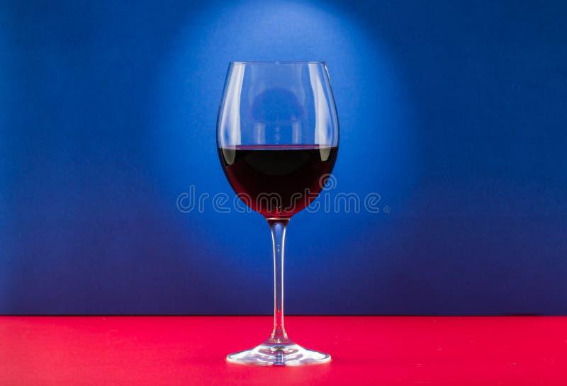 静物画杯与好的光线影响的酒在红色和蓝色背景中 库存图片