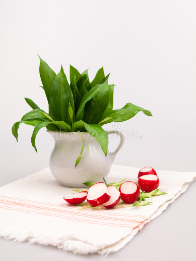 静物画构成用熊的大蒜(葱属Ursinum)和萝卜 免版税库存照片