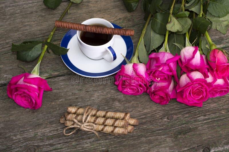 静物画桃红色玫瑰行咖啡和曲奇饼 库存照片