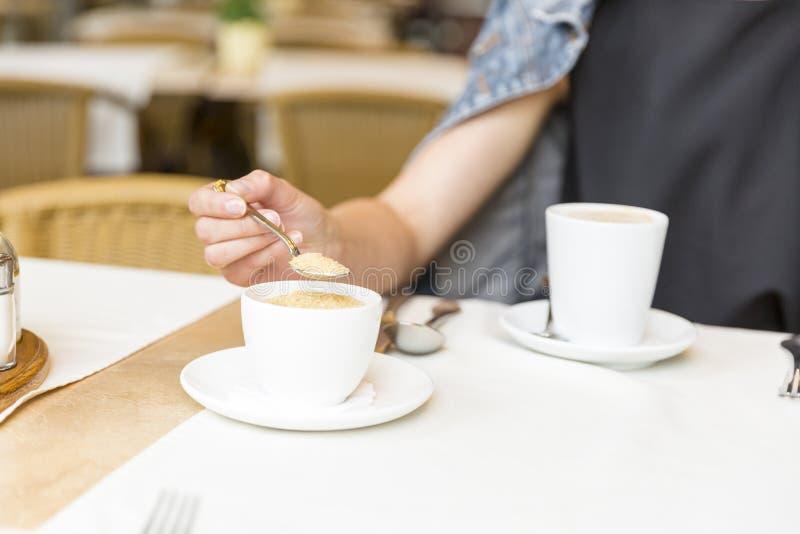 静物画概念 休息在咖啡馆的美丽的女孩,加糖入咖啡 免版税库存图片