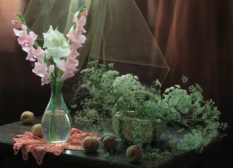 静物画用成熟桃子和剑兰花束  免版税库存图片