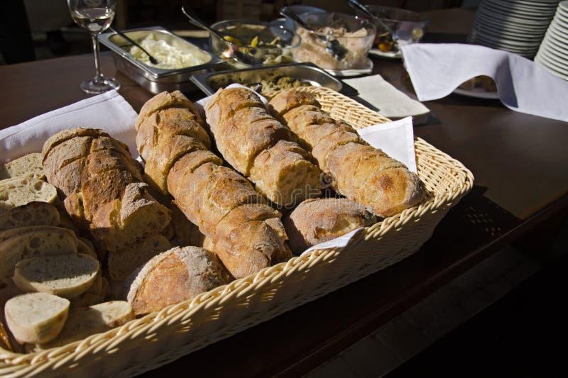 静物画用酥皮点心和面包在柳条筐在木桌上与板材、碗和菜沙拉 免版税库存照片