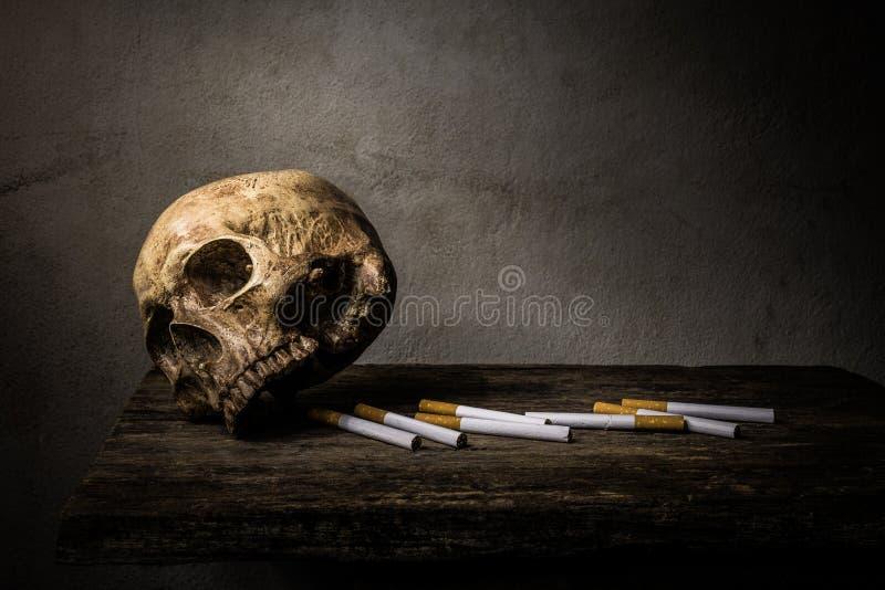静物画头骨和香烟人抽香烟并且有  库存照片