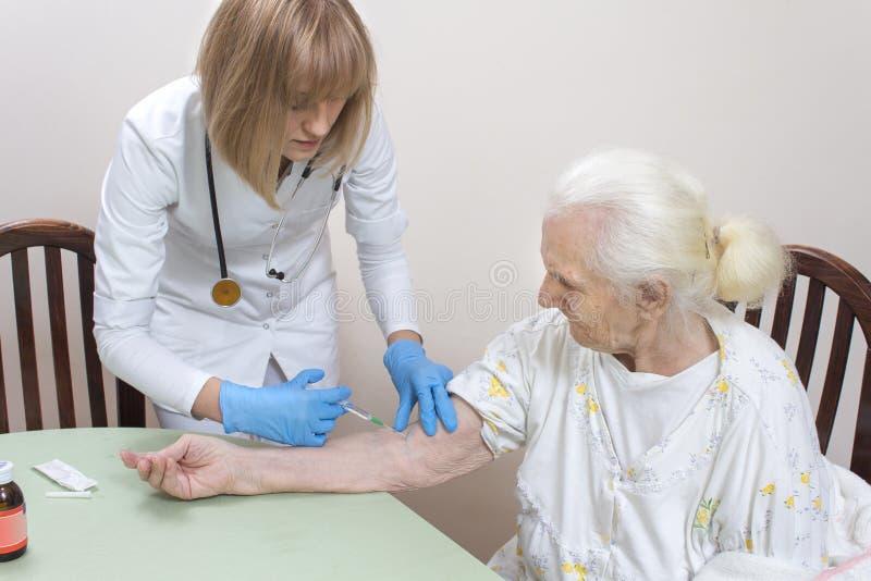 静脉注射到一个非常老妇人的静脉里 一次性手套的护士给医学静脉内在注射器 免版税库存图片