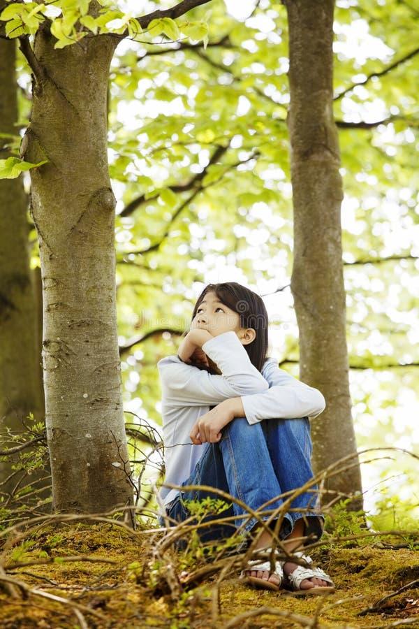 静静地坐森林的女孩新 免版税库存照片