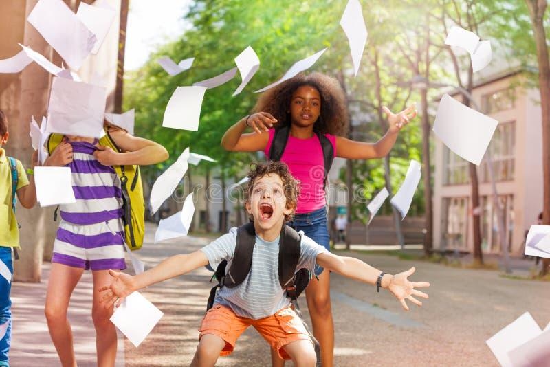 非常与朋友的激动的男孩尖叫投掷纸 免版税图库摄影