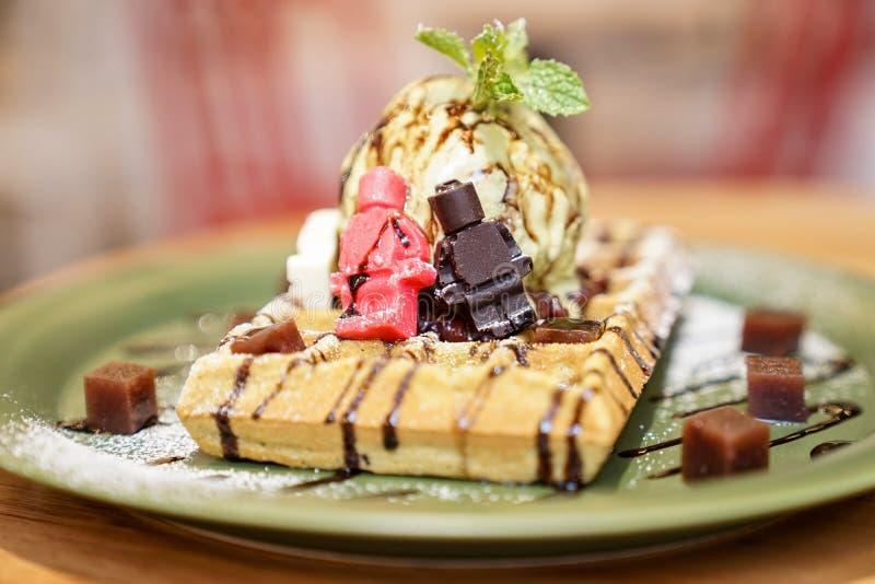 非常与绿茶冰淇淋的鲜美新鲜的奶蛋烘饼在上面,装饰由一点红褐色的白色玩偶白色巧克力和果冻红色 免版税库存照片