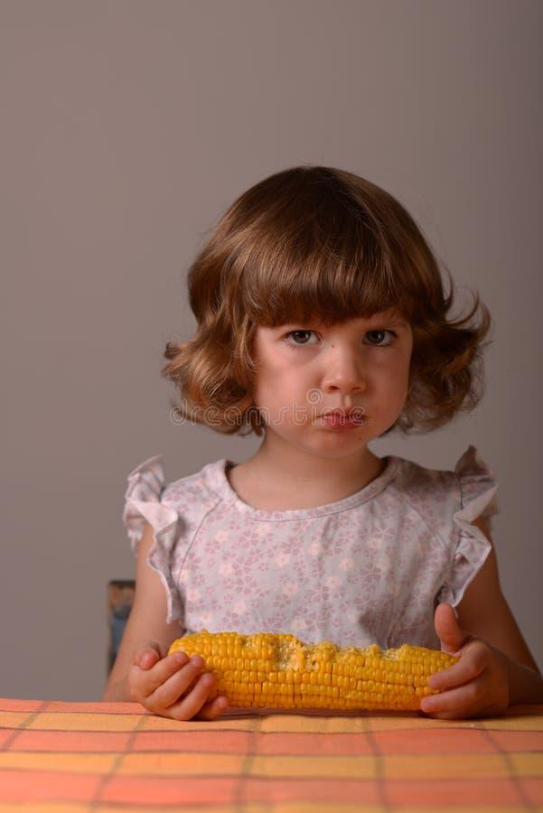 非常严肃的女孩用玉米 免版税库存图片