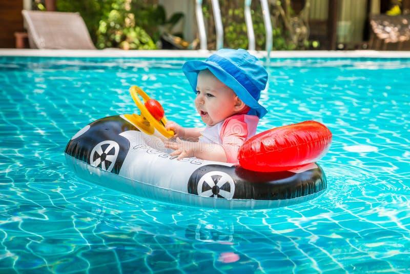 非常在轮子后的快乐和快乐的孩子 r 比一岁的女孩较不是驾驶  图库摄影